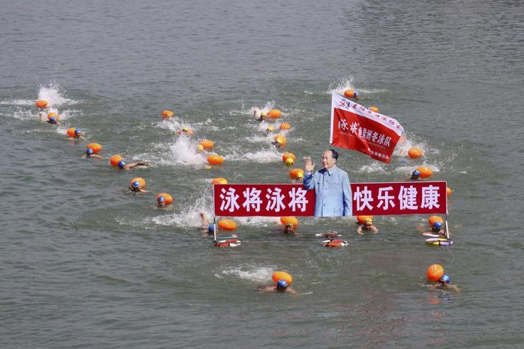 "Participants swim with a portrait of late Chinese Chairman Mao Zedong in the Hanjiang River, a large branch of the Yangtze River in Xiangyang, Hubei province July 12, 2015. Hundreds of residents took part in the event to celebrate the upcoming 49th anniversary of Mao swimming in the Yangtze River on July 16, 1966, local media reported. The words beside the portrait read, ""Swimming champions, be happy and healthy."" REUTERS/Stringer"