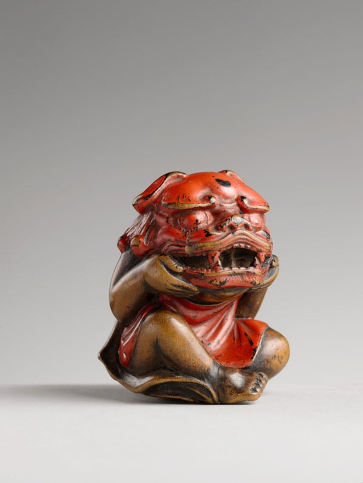 Netsuke, enfant enlevant un masque de Shishi Bois laqué rouge Japon, époque Edo © Raphaël Chipault et Benjamin Soligny / Musée guimet Collections du musée d'Ennery, annexe du musée Guimet