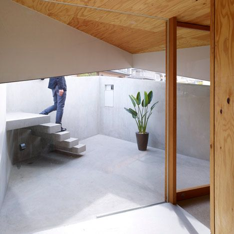 Interior of a house in Hiroshima by Japanese architects Suppose Design Office:  A cantilevered staircase leads down to the sunken main entrance.