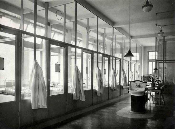 1918 Binnengasthuis kinderafdeling  Zaal in de kinderkliniek van het Binnengasthuis te Amsterdam van buiten gezien, met witte jassen op de gang en een wastafel en zithoek.