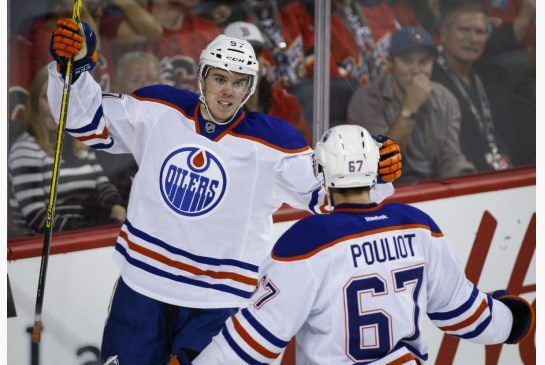 Edmonton Oliers' Connor McDavid, left, celebrates his goal with teammate Benoit Pouliot (67) during second period NHL hockey action against the Calgary Flames, in Calgary, Saturday, Oct. 17, 2015. THE CANADIAN PRESS/Jeff McIntosh