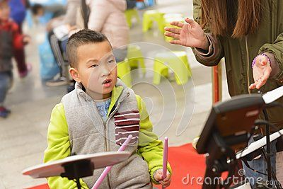 Chinese kid playing percussion instrument outdoor with teacher beat time