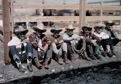 Cowboys and riders sit along a fence at the San Antonio Rodeo Texas 1920 30s