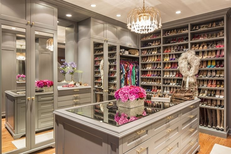 Fabulous closet features gray built-in cabinets accented with brass hardware and mirrored doors flanking mirror over built-in jewelry drawers. A brass chandelier hangs over gray closet island topped with clear glass lined with drawers across from floor to ceiling, built-in shelves for shoes.