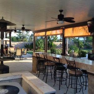 cement-patio-and-swivel-barstools-with-outdoor-kitchen-also-patio-cover-ideas-and-patio-sun-shade-with-ceiling-fan-plus-patio-furniture-and-lawn-with-fence-design-also-enclosed-patio-ideas