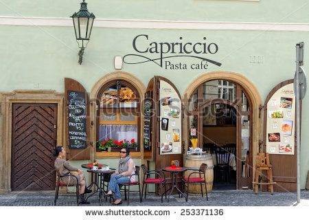 PRAGUE, CZECH REPUBLIC - JULY 3, 2014: People enjoy a cup of a drink at cafe near the Old town square.  - stock photo