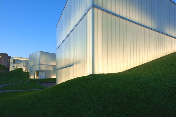 """Πέντε κατασκευές από ματ γυαλί, αναφερόμενες ως """"φακοί"""" από τον αρχιτέκτονα τους Steven Holl, συνδέονται με υπόγειους διαδρόμους και συνθέτουν το κτήριο Bloch, μια προσθήκη του 2007 του Nelson-Atkins Museum of Art στο Kansas City του Μισσούρι. Τα ημιδιαφανή κουτιά φιλτράρουν το φυσικό φως που πέφτει πάνω στα εκθέματα με την βοήθεια ενός προσεκτικά σχεδιασμένου εσωτερικού χώρου που ανακατευθύνει το φως σε κάθε γωνία."""
