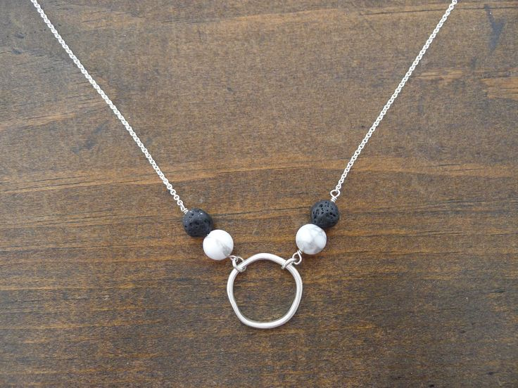 """Wear your favorite essential oils while looking amazing and put together! An organic circle hangs between howlite and lava beads. Hammered silver with a brushed satin finish. 17.5"""" length. Add a drop"""