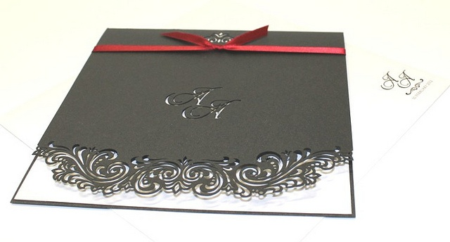 A delicate laser cut metallic charcoal invitation. Includes a laser cut monogram and edging detail. A red accent ribbon is included.