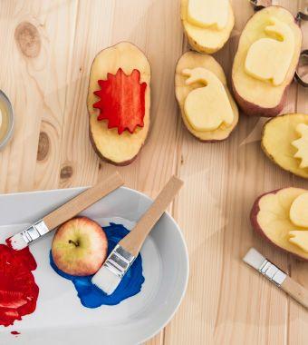Faire des tampons patates avec de la peinture, des pinceaux et des pommes de terre coupées en deux.