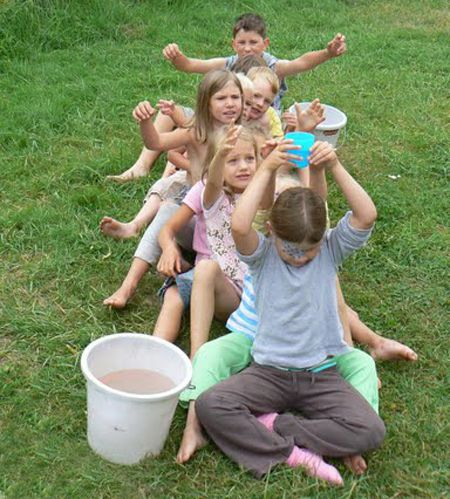 Easy and fun children's birthday game: give a cup with water to the person behind you, but you can only do so by lifting the cup over your head!