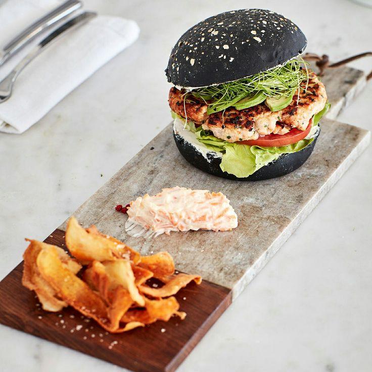 Salmon burger with charcoal bun bread, avocado, sweet lemon mayonnaise, coleslaw and homemade fried potatoes