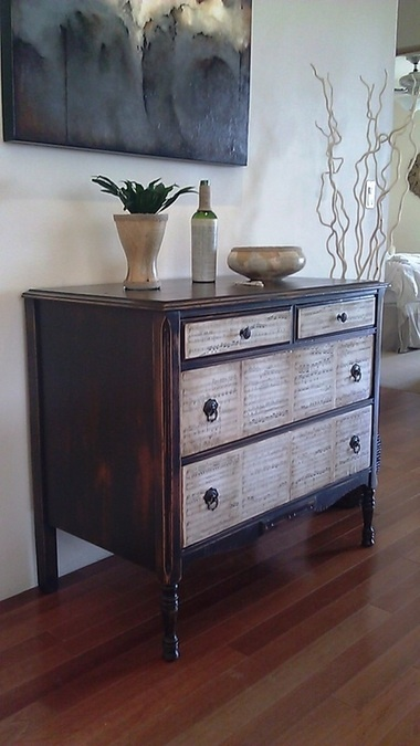 decoupaged sheet music on the drawers - very close but black with glass knobs!