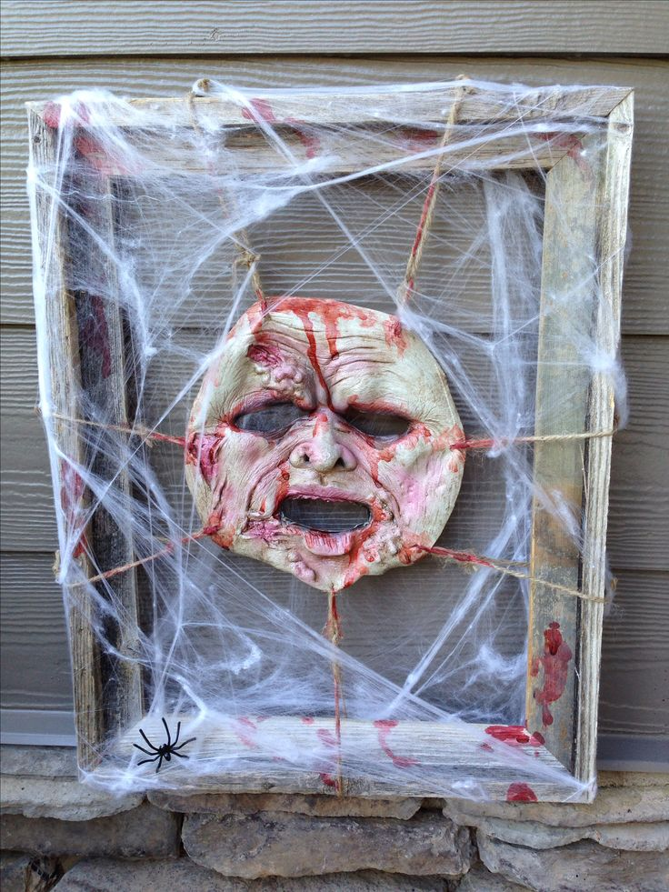 dollar store: rubber mask, frame, twine, and spider webs. Tie the mask to the…