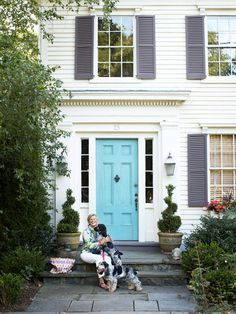 Playful color combination of turquoise door with purple-gray shutters on a very traditional white house.