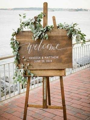elegant wooden wedding welcome sign with eucalyptus leaves on easel
