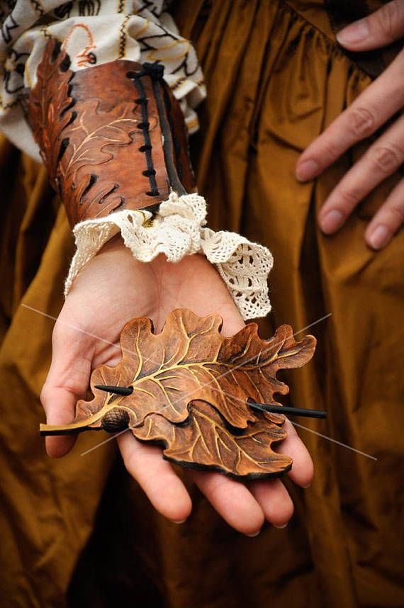 A pair of decorative bracers inspired by the oak tree motif  Its one of ours best designs. Very beautiful and laborous leatherworked. Thick leather carved and deeply punched (and painted). You can hang your pitbull with his teeth on this piece of art! :)  It can be in brown, green, or metallic version - you choose.  Designer: Magdalena