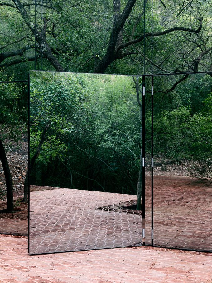 Mexican architect Tatiana Bilbao has used mirrored glass, along with rammed earthand clay bricks, to create a vacation home that blends with its wooded site in Monterrey. Los Terrenos, or The Terrains, is located on a forested hillside in the northern Mexican city. The residence is near another project by Bilbao, the Ventura House, which consists of an assemblage of concrete volumes that emerge..