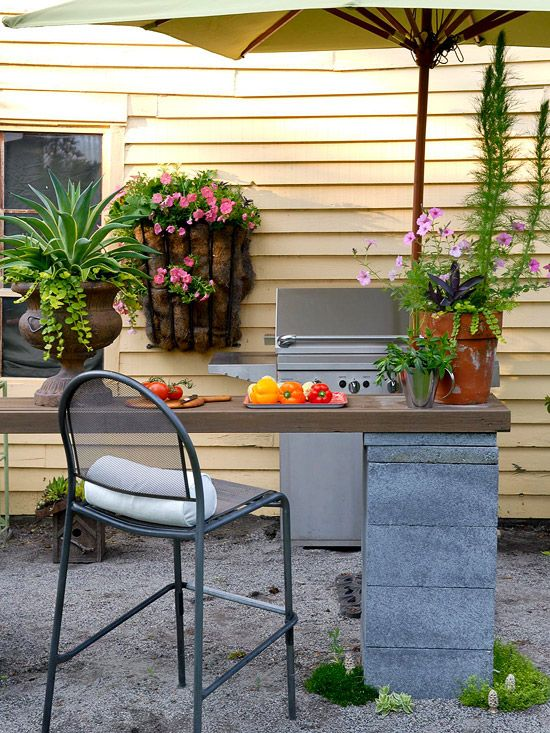 Outdoor Kitchen... A spacious counter for cooking and entertaining --made of recycled wood and cinder blocks -- cost almost nothing. Originally, the cinder blocks were part of the chimney at the back of the house. Decorative painting gave them a pleasing gray patina.