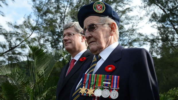 Hong Kong Veteran Arthur Kenneth Pifher, 91, of Grimsby, Ont., walks with Prime Minister Stephen Harper at a Remembrance Day ceremony at Sai Wan War Cemetery in Hong Kong.