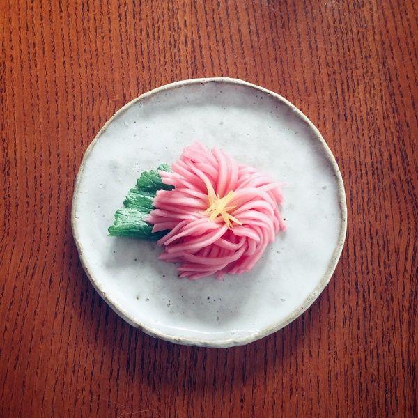 かぶを菊の花に見立てた菊花蕪(きっかかぶら)。おせちだけではなく、ふだんのおかずにも。細く切ったかぶの食感が楽しいひと品です。  かぶは皮をむき、根元を5mmほど残して細かく包丁を入れます。かぶを90度回転させて、同様に切り込みを入れます。かぶに格子状の切れ込みが入った状態です。  漬け汁を作ります。鍋に塩、砂糖、みりん、水を入れて煮立てて塩と砂糖を溶かして少し煮詰めます。あら熱が取れたらお好みのお酢(赤くしたかったので梅酢と柿酢を使いました)を加えます。  保存容器にかぶを入れ、漬け汁をひたひたまで加えて冷蔵庫へ。1日くらいおいてからが食べごろです。器に青菜を敷き、かぶをのせてゆずの皮を中心においていただきます。