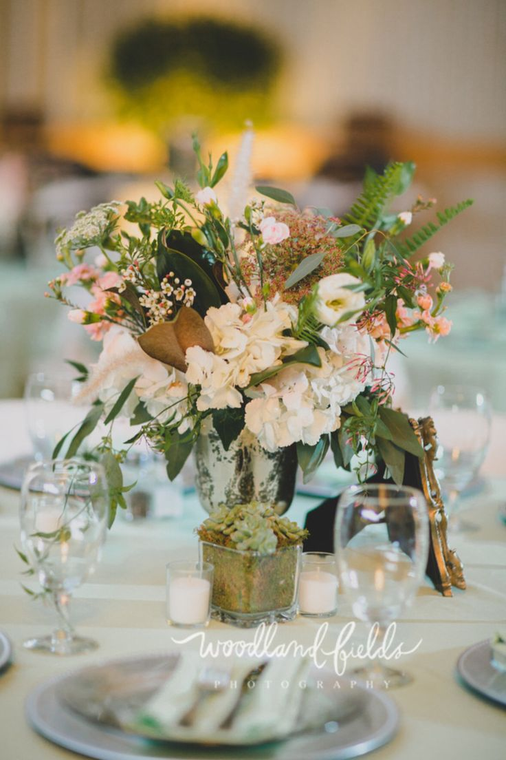 arrangement of white hydrangea, chocolate queen anne's lace, white queen anne's lace, white lisianthus, mini pink carnations, peach stock, fern, jasmine trails, white fountain grass and white wax flower in tall footed mercury glass containers adorn half the tables at the reception. they are accented by a succulent in small cube with moss