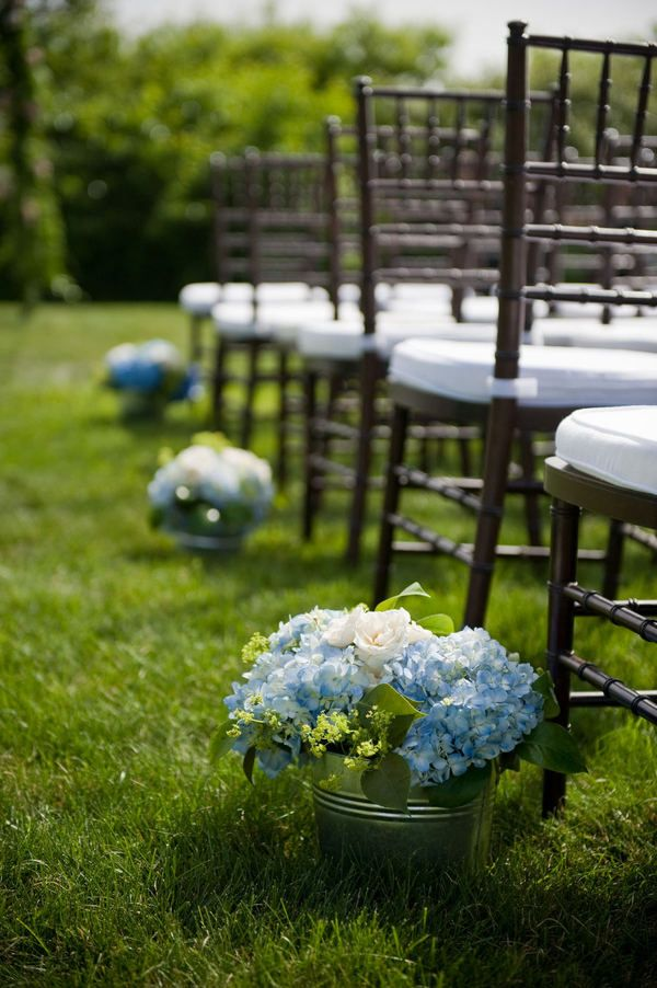 Great idea for aisle flowers that can be reused as centerpieces.  Love the blue hydrangea softened by spray roses and bupleurum.