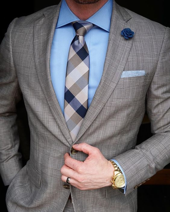Acheter la tenue sur Lookastic: https://lookastic.fr/mode-homme/tenues/costume-chemise-de-ville-cravate/20591 — Chemise de ville bleue claire — Broche à fleurs bleue marine — Cravate en soie à carreaux brune — Pochette de costume bleu clair — Costum