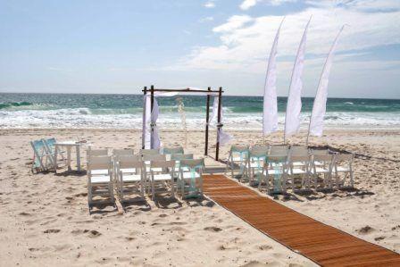 Eternal Weddings Décor Photography. Gold Coast. Beach Ceremony. Bali Flags. Bamboo aisle runner. Wedding Arbour. White Americana Chairs. Blue Chair Sash. Signing Table. Seashell Chandelier. Seashells. Beach. Sand