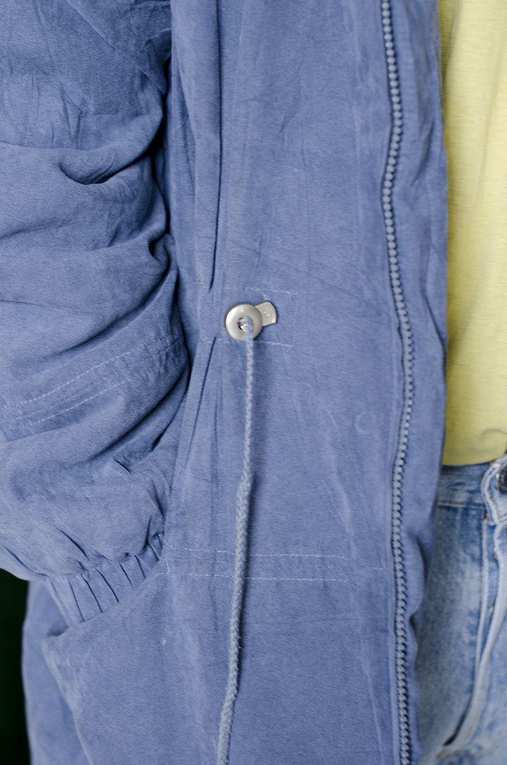 Chaqueta larga en tela tipo terciopelo con relleno color azul claro con cremallera frontal, bolsillos frontales a la altura de la cadera. Forro en un poliester azul oscuro.