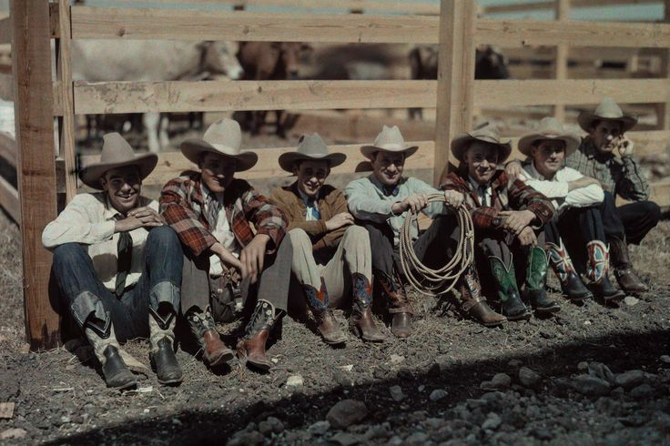 Cowboys and riders sit along a fence at the San Antonio Rodeo in Texas, 1928