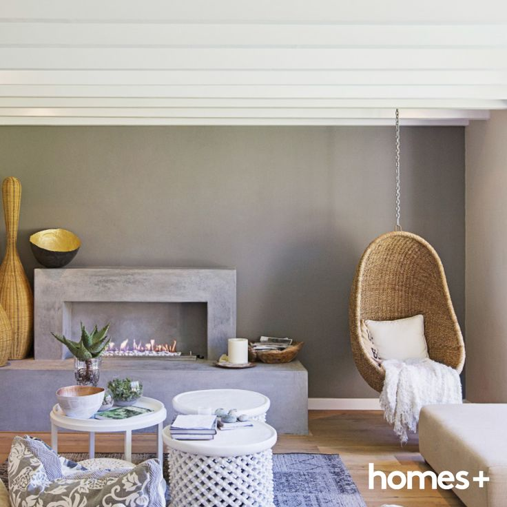 #beachhouse #livingroom #hangingchair #white #fireplace #stool #table #rug #plant #interior #style #home #homesplusmag #cushion #candle