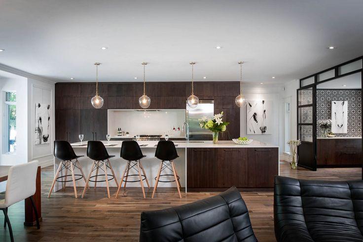 Une cuisine moderne avec un style équestre. Les armoires de cuisine sont en bois de noyer teint et les comptoirs en quartz.