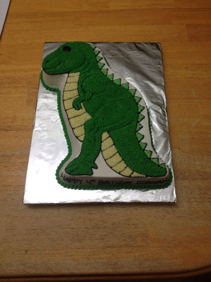 Dinosaur made using Wilton dinosaur pan. White, lemon yellow (very pale), kelly green mixed with leaf green (pale for spikes, dark body and edging), black outlining and lettering
