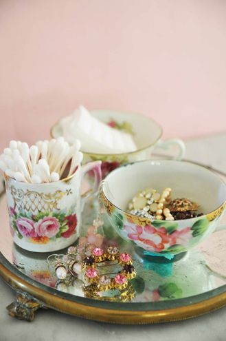 Vintage teacups and mirror hold bathroom items and jewelry