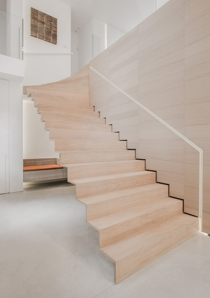This contemporary floating wooden staircase looks like it was pulled out of the veneer clad wall