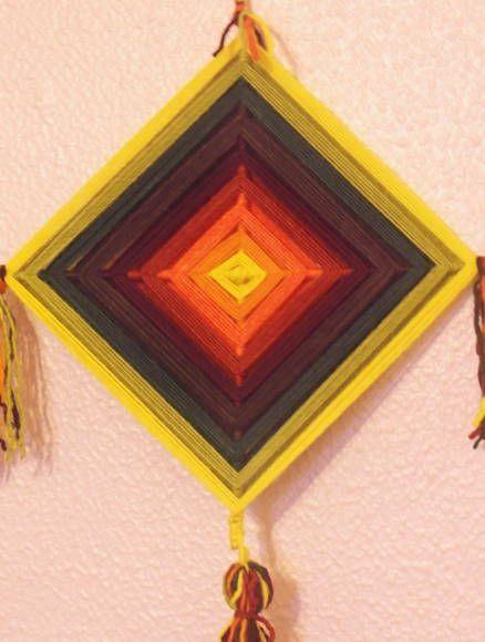 """Mandala de 4 pontas, produzida com lã 100% natural sob base de varetas de bambus de 0,5cm.  Ojo-de-Dio é a mandala de 4 pontas produzida pelo povo Huichol, do México. eles consideram o olho-de-deus um portal mágico através do qual a humanidade e a divindade percebem um ao outro.  Os Huichóis também chamam o Ojo-de-dio de Sikuli, que significa """"o poder de ver e compreender coisas desconhecidas""""."""