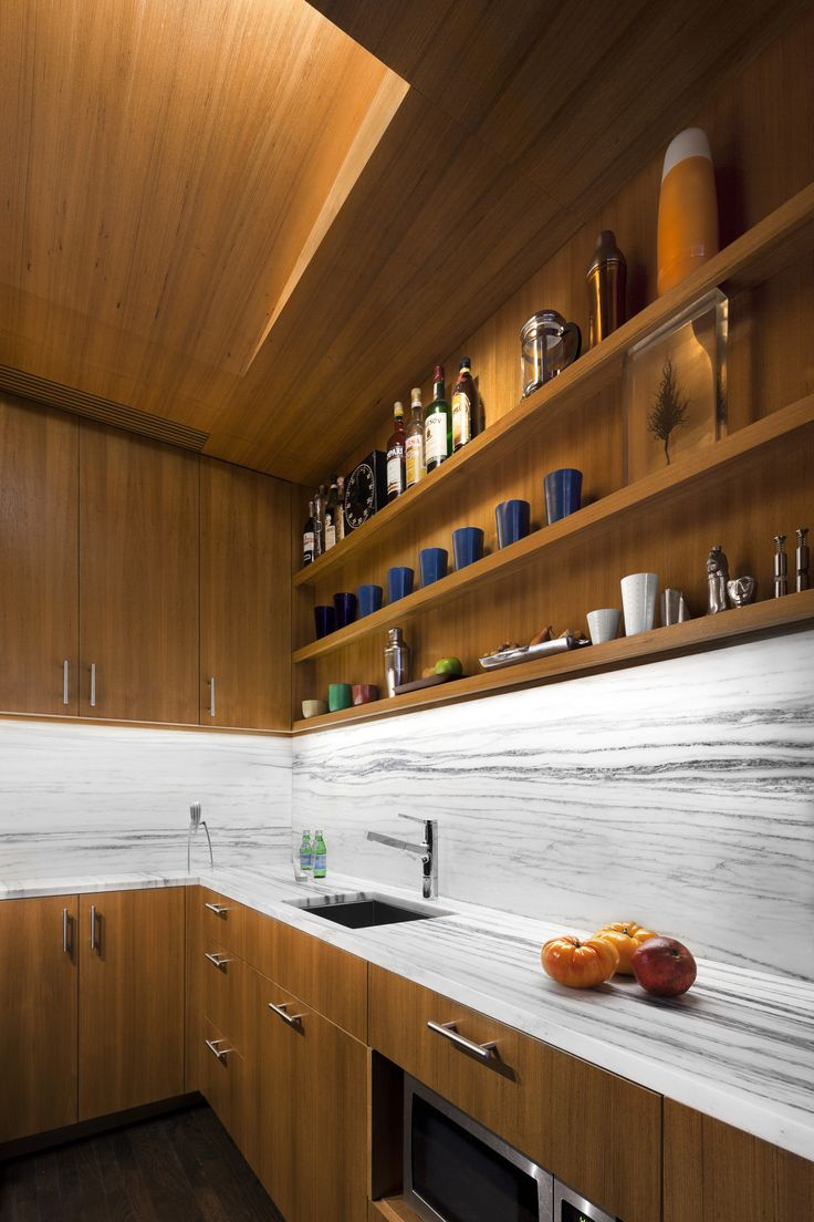 An LED strip is concealed in the angled ceiling plane; the supply air diffuser, also of teak, is barely visible over the counter. The microwave is tucked under a drawer below the counter.