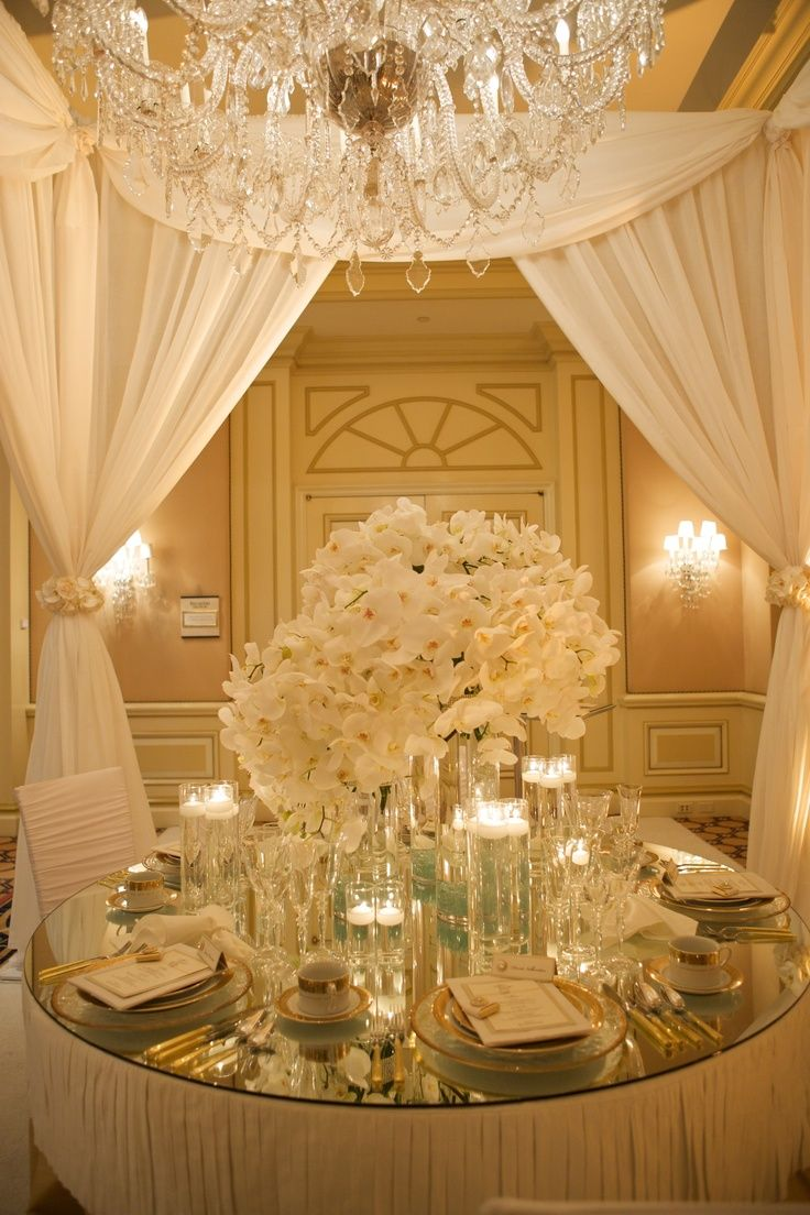 Gold and white wedding table settings Gold rim plates, cups and cutlery with golden handles on a mirrored table top with a lavish centerpiece of White Phalaenopsis Orchid spells luxury like no other.