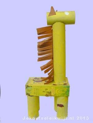 GIraffe 1  5 wc rollen      keuken rol      gele verf      bruine verf      lijm      lege hagelslag verpakking      bruin papier    Verf de 5 wc rollen, keukenrol en hagelslag verpakking geel met plakaat verf. Terwijl de verf opdroogd knip je een brede strook ve stuk bruin papier. Knip de strook in, laat tussen de inkepingen ongeveer 1 cm over. Je gebruikt de strook later als nek haren.  Als de verf droog is plak je 4 wc rollen op de lege verpakking, dit worden de poten vd giraf.
