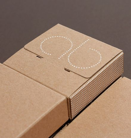 Bespoke Kraft board packaging for luxury jewellery designer with white foil-blocked logo on lid.