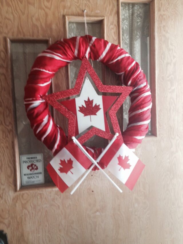 Canada day wreath. Pool noodle, red and white scarves, flags and wooden decoration.