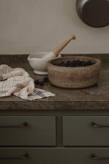 Bastanta bänkskivor i sten och trä ger köket en rustik känsla.