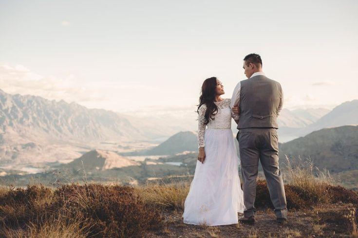 queenstown new zealand wedding couple standing on coronet peak with mountain views by queenstown wedding photographer