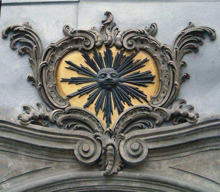 """""""La simbologia nascosta del Sole nero""""  Al numero 8 della Celetná Ulice, sul portale di una casa gotica, l'insegna della casa """"U cerného slunce"""" (al sole nero) brilla dentro un cartiglio barocco riccamente adornato. Anche se questa casa è una delle più famose di Praga, il suo significato non è scontato. Collocata lungo la Via Reale, possiede anche un significato ermetico: se il Sole viene tradizionalmente associato all'oro, il sole nero, nei testi alchemici, è l'allegoria della materia…"""