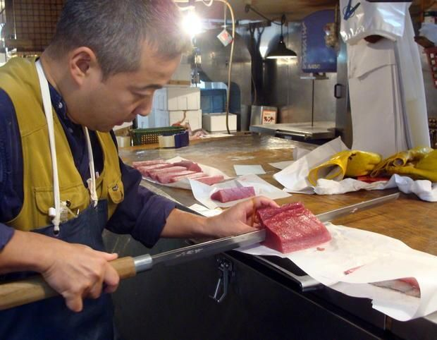 """A worker slices pieces of tuna using a """"Maguro bōchō"""" (tuna knife). The tuna cutters have an extremely long, narrow blade, and a long handle."""
