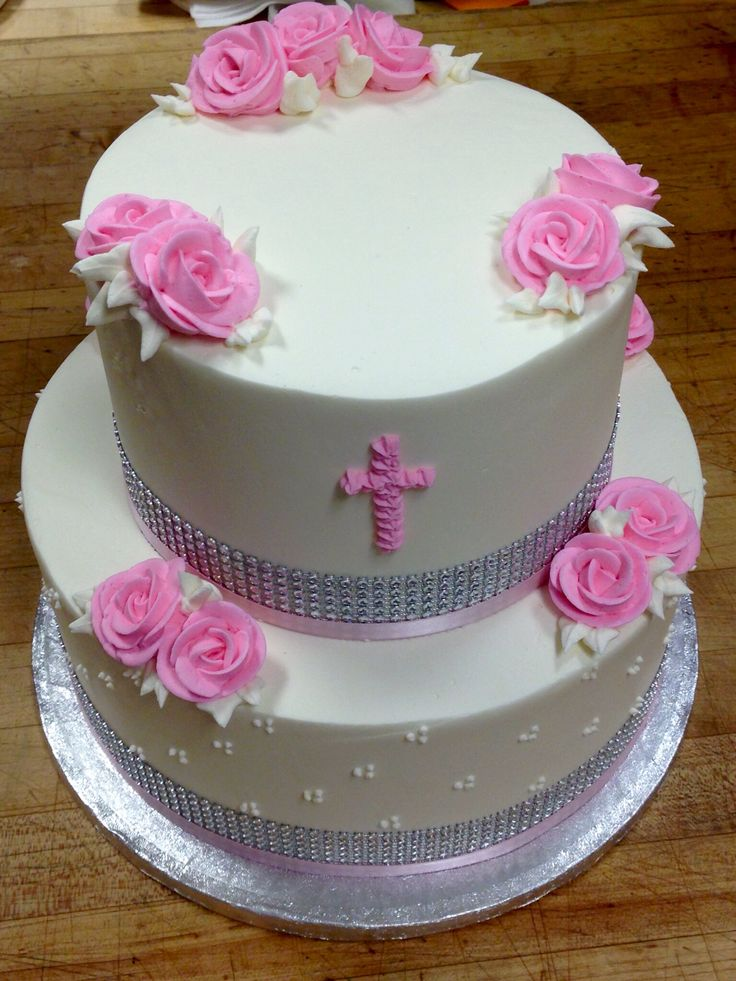 Tiered First Communion cake to serve 30, golden yellow cake filled with chocolate mousse & mini choc. chips, frosted with European buttercream. A pink cross and floral accents add a feminine touch.