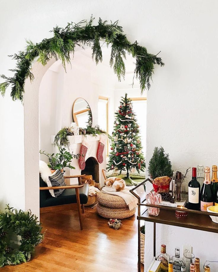 Instagram photo by @westelm • 21.3k likes - Christmas garland greenery hanging from a midcentury arch between two rooms. Suspended how? Holiday decorating at its best.