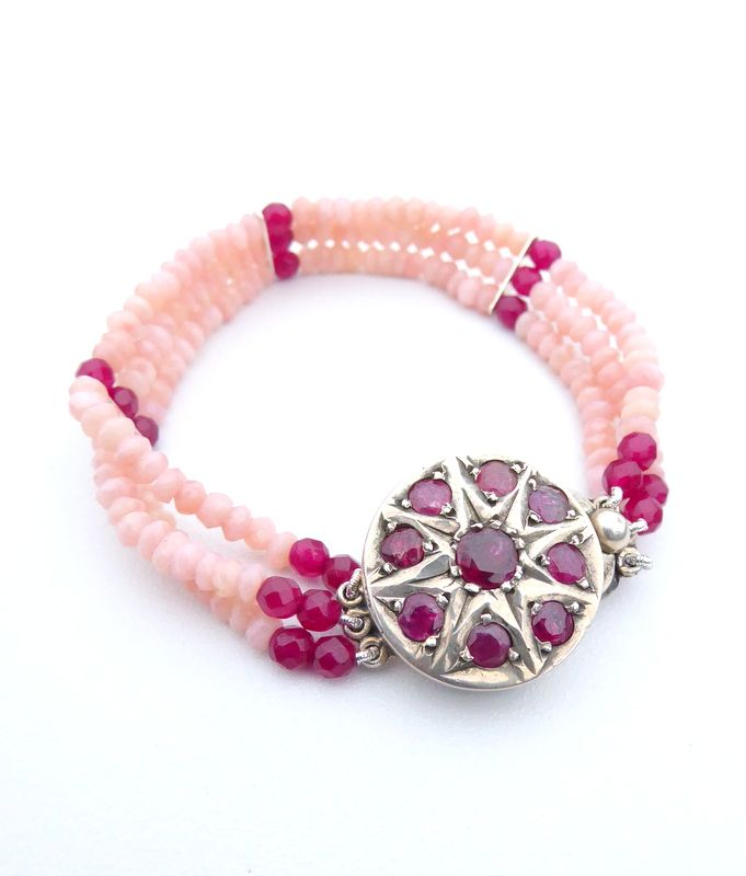 The bracelet contains pink opals and rubies connected to a vintage sterling silver clasp containing rich coloured rubies.