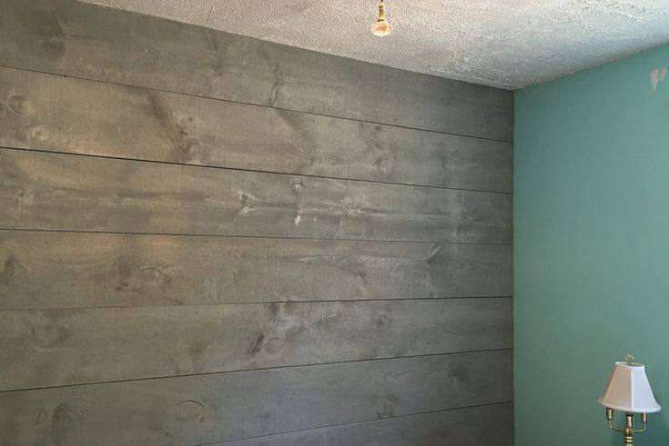 Shiplap wall stained in drift wood grey for a coastal feel. Bedroom painted in a ocean blue trikes out in white
